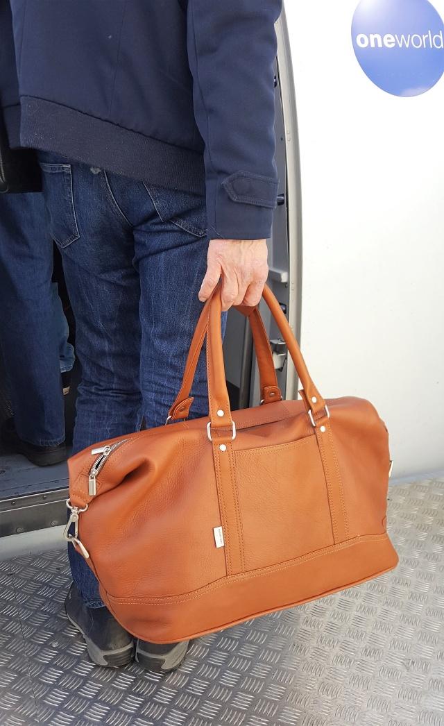 Passagier mit Reisetasche geht an Bord eines Flugzeugs